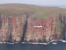 The OY-PHK flying around Hoy Island